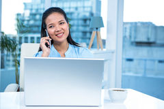 Smiling businesswoman on phone using laptop Royalty Free Stock Photo