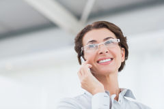 Smiling businesswoman on the phone wearing eye glasses Royalty Free Stock Photo