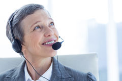 Smiling businesswoman phoning with headphone Stock Photography