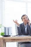 Smiling businesswoman phoning at work. In the office Royalty Free Stock Photography
