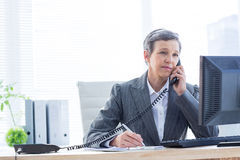 Smiling businesswoman phoning and writing Stock Image