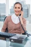 Smiling businesswoman picking up the phone Stock Images