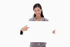 Smiling businesswoman pointing at blank sign board. Against a white background Royalty Free Stock Image