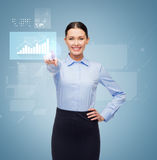 Smiling businesswoman pointing finger to button Stock Photos