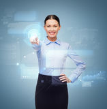 Smiling businesswoman pointing finger to button Royalty Free Stock Image