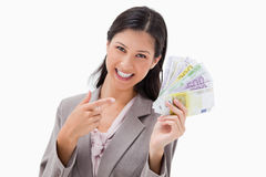 Smiling businesswoman pointing at her money Stock Photo