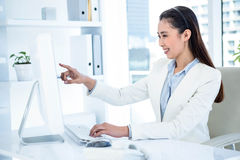 Smiling businesswoman pointing her screen Stock Image