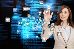 Smiling businesswoman pointing to app icon Royalty Free Stock Images