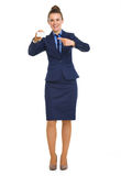 Smiling businesswoman pointing to business card Stock Photo