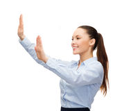 Smiling businesswoman pointing to something. Business and future technology concept - smiling businesswoman pointing to something or pressing imaginary button Stock Photography