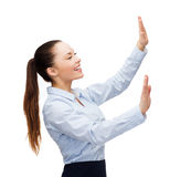 Smiling businesswoman pointing to something. Business and future technology concept - smiling businesswoman pointing to something or pressing imaginary button Stock Image