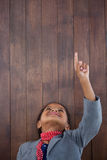 Smiling businesswoman pointing up wards while standing with head back. Against wooden wall Royalty Free Stock Images