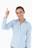 Smiling businesswoman pointing upwards Stock Photo