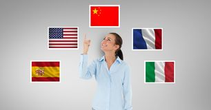 Smiling businesswoman pointing upwards standing by flags against gray background Royalty Free Stock Images