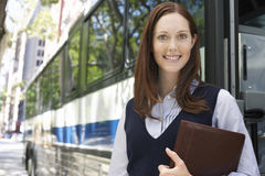 Smiling Businesswoman With Portfolio By Bus. Portrait of a smiling young businesswoman holding portfolio by bus Royalty Free Stock Images
