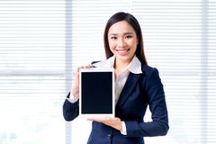 Smiling businesswoman portrait in office standing by window showing screen of digital tablet. Stock Image