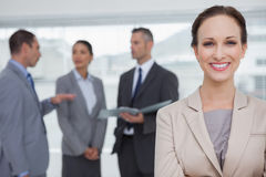 Smiling businesswoman posing while colleagues talking together Stock Images