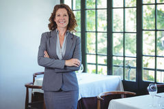 Smiling businesswoman posing with crossed arms. In a restaurant Stock Images