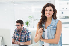 Smiling businesswoman posing with her partner behind her Royalty Free Stock Photography