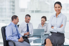 Smiling businesswoman posing while workmates talking together Royalty Free Stock Photos