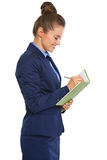 Smiling businesswoman in profile standing, writing in notebook Stock Photo