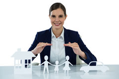 Smiling businesswoman protecting paper cut out family, house and car with hands Stock Photos
