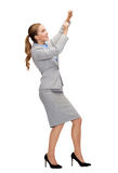 Smiling businesswoman pulling imaginary rope Royalty Free Stock Image