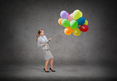 Smiling businesswoman pulling rope with balloons Stock Photography