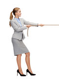 Smiling businesswoman pulling rope. Business and education concept - smiling businesswoman pulling rope Royalty Free Stock Photography