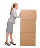 Smiling businesswoman pushing tower of cardboards. Business, post and transportation concept - smiling businesswoman pushing tower of cardboards Royalty Free Stock Photography