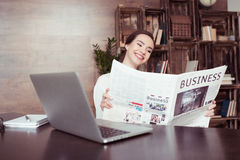 Smiling businesswoman reading newspaper at desk with laptop Royalty Free Stock Image