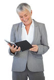 Smiling businesswoman reading notepad Stock Image