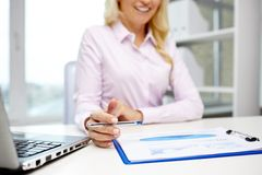 Smiling businesswoman reading papers in office stock images