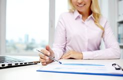 Smiling businesswoman reading papers in office Stock Photo
