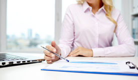 Smiling businesswoman reading papers in office Stock Photos