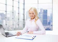 Smiling businesswoman reading papers in office Royalty Free Stock Photo