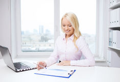 Smiling businesswoman reading papers in office Royalty Free Stock Photos