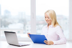 Smiling businesswoman reading papers in office Stock Image