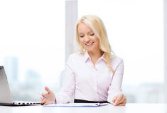 Smiling businesswoman reading papers in office Royalty Free Stock Image