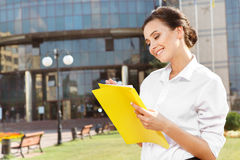 Smiling businesswoman reading papers outdoors Stock Image