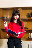 Smiling businesswoman in a red blouse with  folder of documents Royalty Free Stock Photography