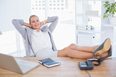 Smiling businesswoman relaxing on her office Stock Image