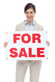 Smiling businesswoman with for sale sign. On white background Royalty Free Stock Images