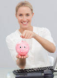 Smiling businesswoman saving money in a piggibank Stock Photography