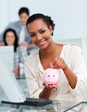 Smiling businesswoman saving money in a piggy-bank Stock Image