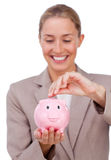 Smiling businesswoman saving money in a piggybank. Isolated on a white background Royalty Free Stock Photography