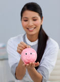 Smiling businesswoman saving money in a piggybank. In the office Stock Images