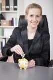 Smiling Businesswoman Saving Money to Piggy Bank Stock Image