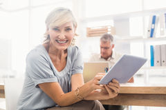 Smiling businesswoman scrolling on a tablet Stock Photo