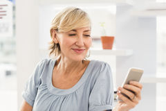 Smiling businesswoman sending a text Royalty Free Stock Photo
